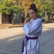 Chana in karate gi with purple belt demonstrating a martial arts stance