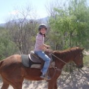 Abby wearing helmet riding horse