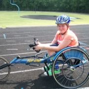 Catherine in her sports wheelchair on a fitness track