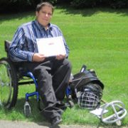 Corey in wheelchair next to his new sports equipment