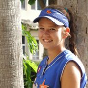 Julia smiling proudly in her softball uniform
